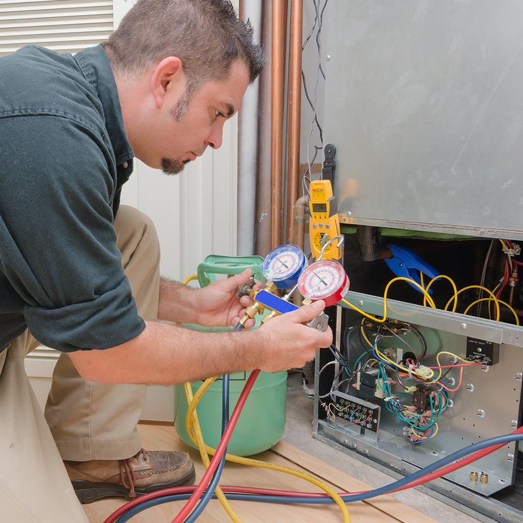 Service Technician fixing furnace.